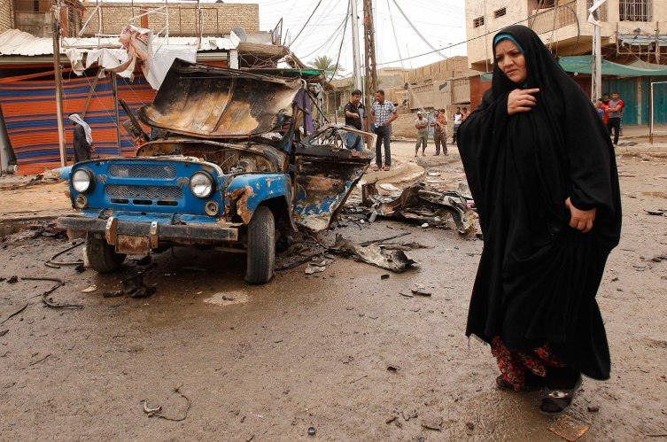 An Iraqi woman passes by the scene of a car bomb attack in the Kamaliyah neighborhood, a predominantly Shiite area of eastern Baghdad, Iraq, Monday, May 20, 2013.