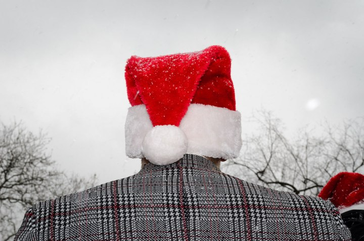 A man in a Santa hat in Tompkins Square Park.