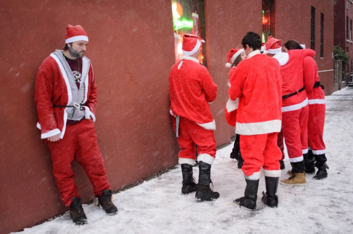 SantaCon participants take a break from the bar crawl in the East Village.