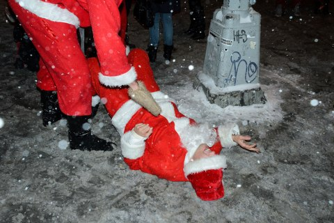 A SantaCon participant lends a helping hand to a fellow Santa after he slipped on the ice on Second Ave.