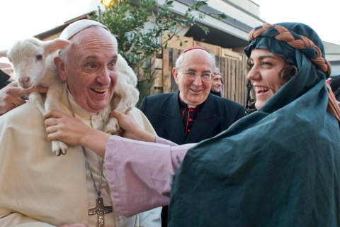A woman dressed as a character from the nativity scene puts a lamb around the neck of Pope Francis as he arrives to visit the Church of St Alfonso Maria dei Liguori in the outskirts of Rome, on Jan. 6, 2014.
