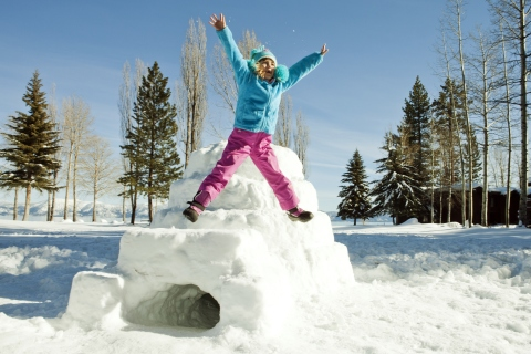 Young girl jumping next to an igloo