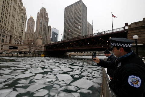 A police officer stops to photograph the cracked ice in the Chicago River