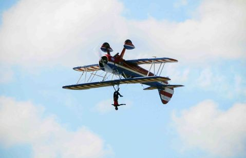 """U.S. pilot Greg Shelton and wing walker Ashley Battles performs a stunt called Wing Walker during the """"Ilopango Air Show 2014"""", in the air base of Ilopango city, in San Salvador, El Salvador, on Jan. 26, 2014."""