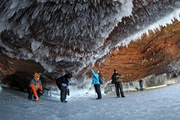Sightseers crouch to avoid icicles in a sea cave on frozen Lake Superior at the Apostle Islands National Lakeshore