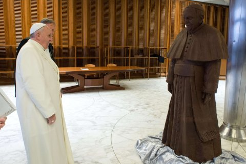 Pope Francis looks at a chocolate statue of himself, given to him after his weekly audience, on Feb. 6, 2014.