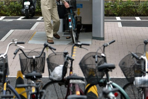 "A MAN TAKES A BICYCLE OUT OF THE ""ECO CYCLE"" PARKING IN TOKYO."